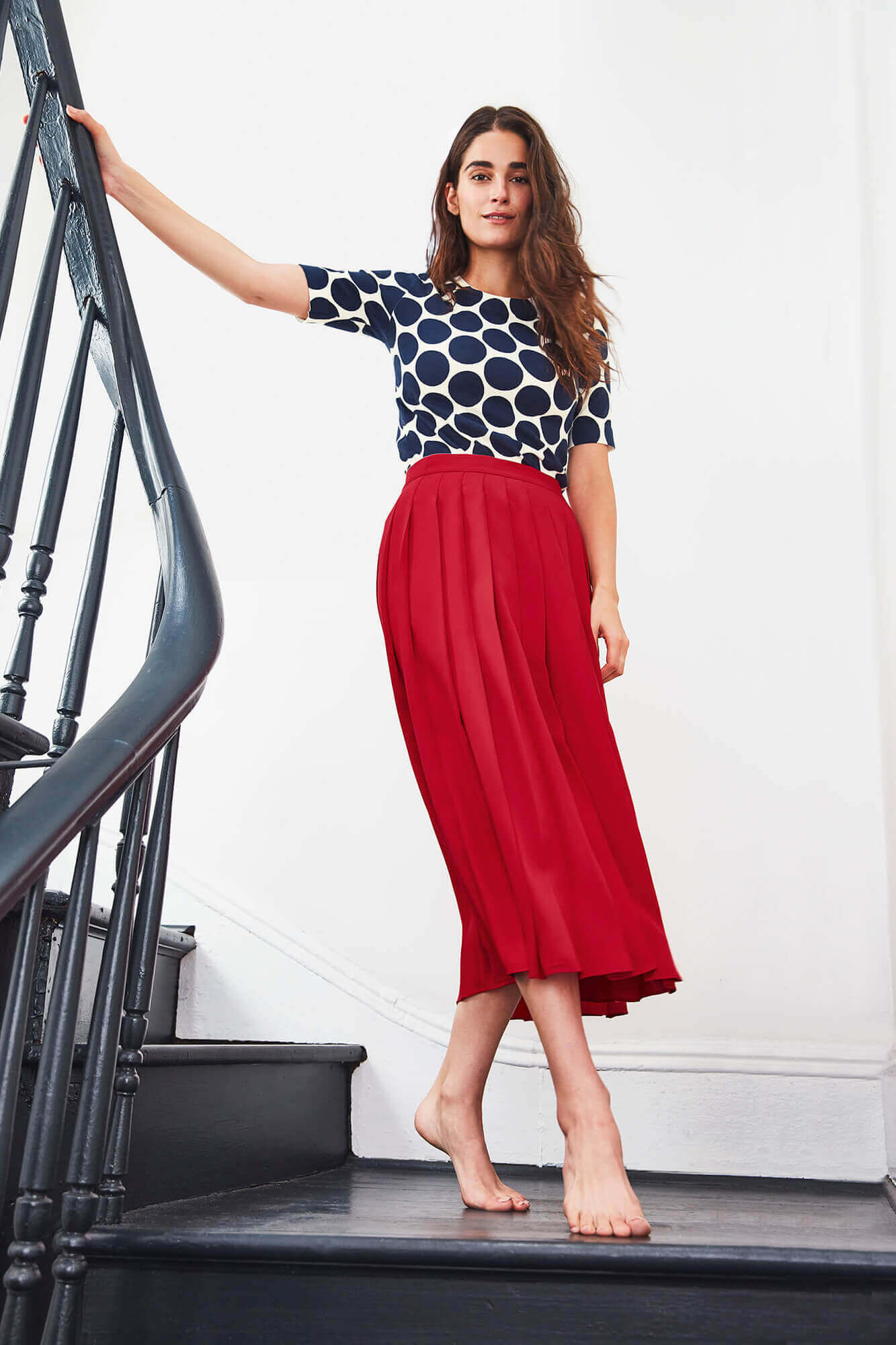 Young brunette wearing red skirt and polka dot shirt