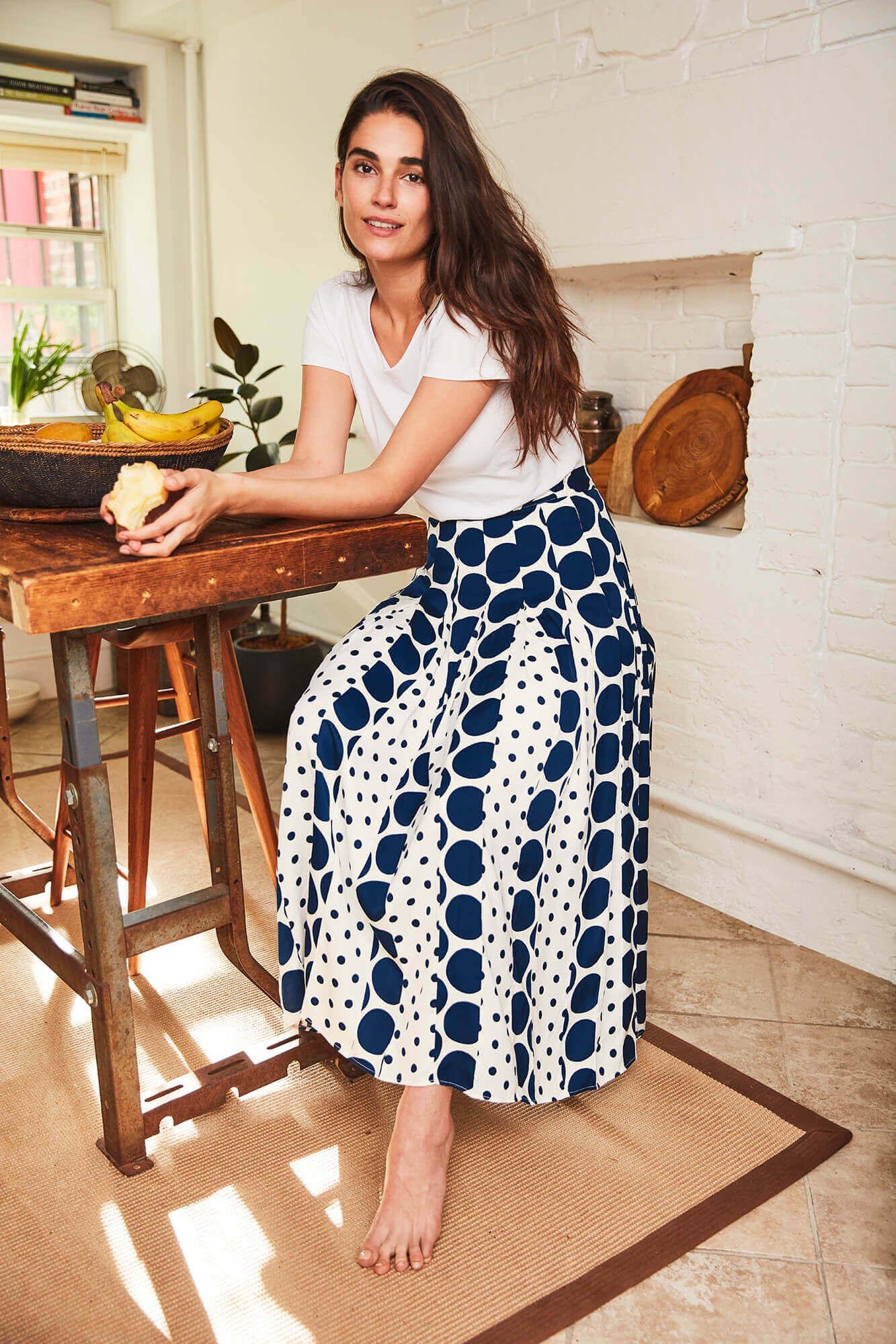 Young brunette wearing polka dot skirt and white blouse