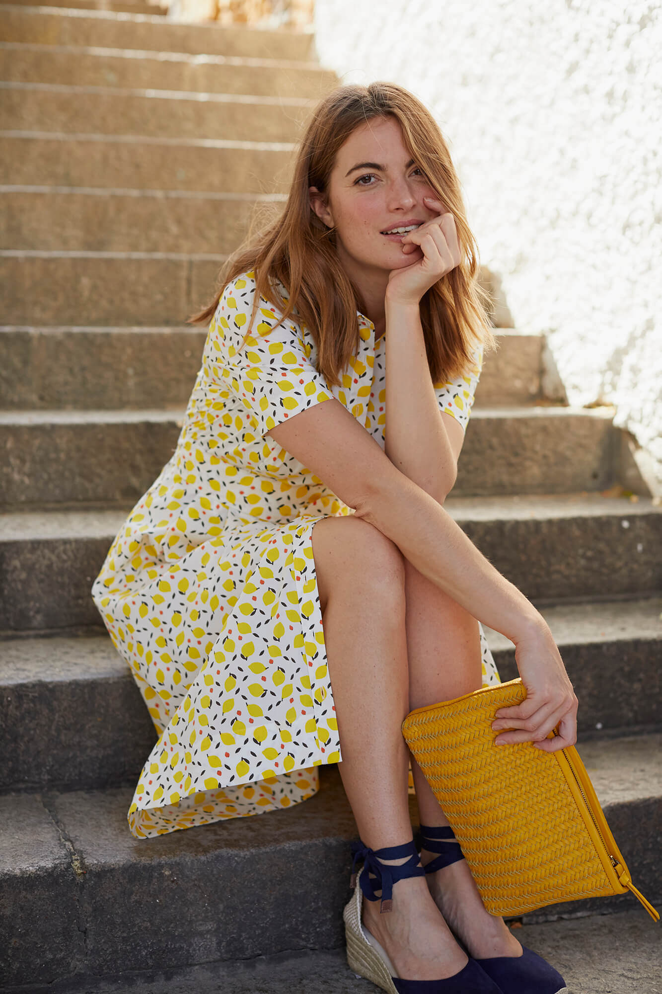 Girl in a yellow dress and bag sitting on a stairs