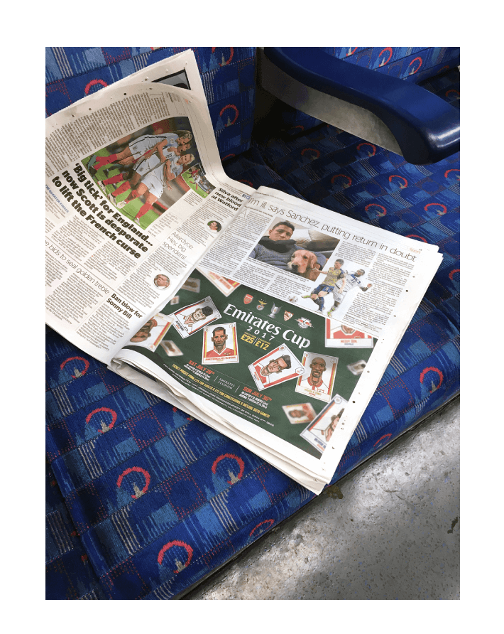 Arsenal ad prepared by Rhapsody is placed in a newspaper laying on a train seat